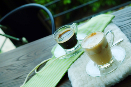 Hot Cappuccino Coffee and Hot Americano coffee on wooden table with cozy coffee shop.have some space for write wording