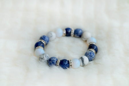 Blue and white color tone lucky fortune stone bracelet include which Lapis lazuli, Sodalite, Howlite and Moonstone on white wool background. Amulet accessories for good lucky fortune and happy life