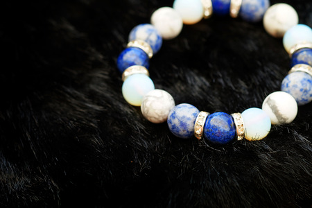 Blue and white color tone lucky fortune stone bracelet include which Lapis lazuli, Sodalite, Howlite and Moonstone on black wool background. Amulet accessories for good lucky fortune and happy life Stock Photo