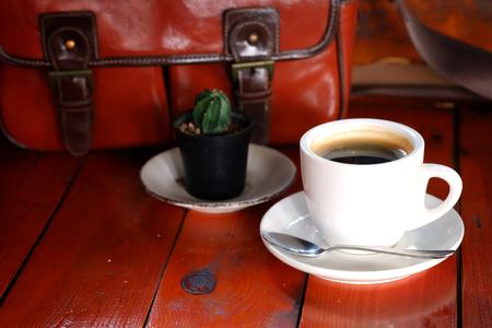 Hot Black Americano coffee in white cup with vintage brown leather bag on teak wooden background. have some space for write wording Reklamní fotografie