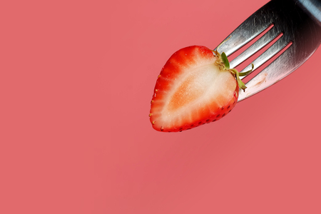 fondue strawberry soaked in hot black chocolate on a fork with pink background with minimalist style .have some spec for write wording Stock Photo