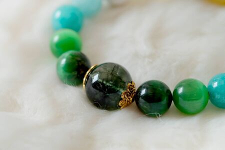 Green and white tone lucky stone bracelet. green moss agate, Green tiger's eye, jade on white wool background. supplement Fortify Fortunate charm and rich Stockfoto
