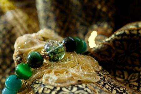 Green and white tone lucky stone bracelet. green moss agate, Green tiger's eye, jade on Thai traditional golden tone fabric background. supplement Fortify Fortunate charm and rich