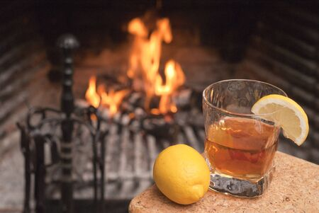 Glass with a drink, a segment of a lemon and the whole lemon against burning in a fireplace fire wood