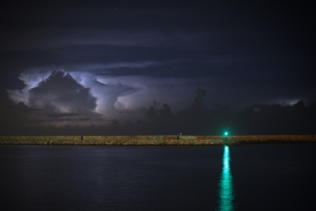 Green beacon over water against the storm sky