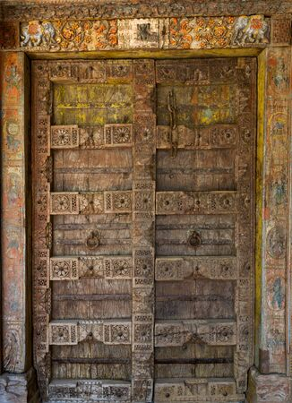 Carved wooden door to the temple with bas-reliefs and the remains of a color list