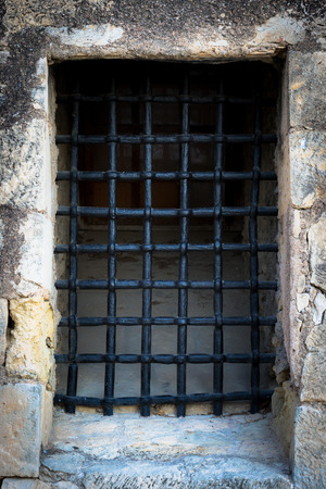 medieval blacksmith: The forged black lattice on the window in a stone wall.