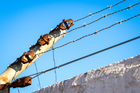 aciculum: Steel rusty barbed wire on a support against the sky Stock Photo