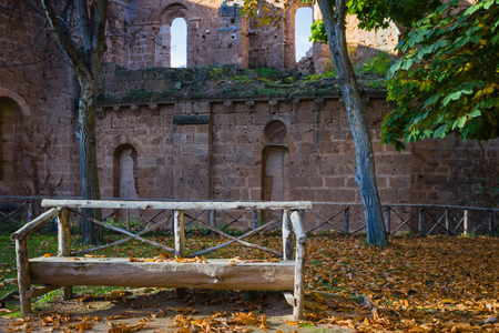 autumn colour: Wooden bench against a half-ruined wall of the monastery in the fall.