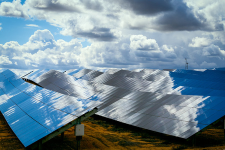 Silicon panels of solar batteries against the cloudy sky in the middle of the day.