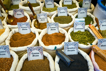 Multi-colored tasty spices with plates on which are written names of herbs and plants.