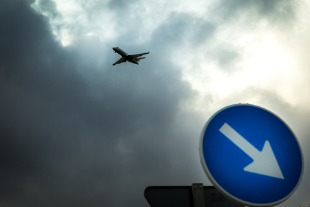 The plane in the cloudy sky, in the foreground the dolozhny sign only to the right