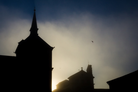 Dark silhouette of the temple against the background of the light golden morning sky with a silhouette of a bird.