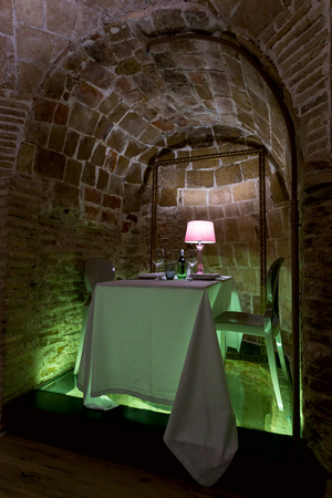 The table served in a stone arch for a romantic dinner. Stock Photo