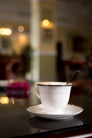 White cup on the chtol against the background of the spacious hall.
