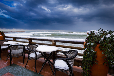 The snow which has covered furniture on the embankment of the warm sea