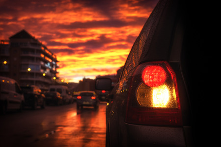 Tail light of the car against the background of the street lit with light before sunset reflected from bright clouds. Stock Photo