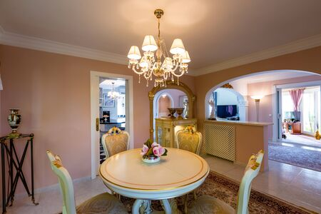 Dining room in classical style, light furniture, marble, luxury. General view on the room, furniture, accessories, style. Standard-Bild