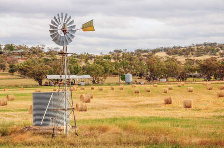 windmill in the field with hay and straw bales in the end of summer