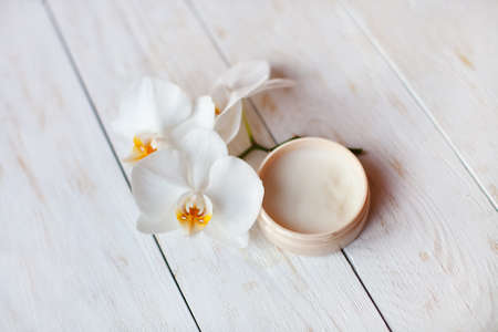 exotic flower: face cream with white orchid on white wooden table. Close up