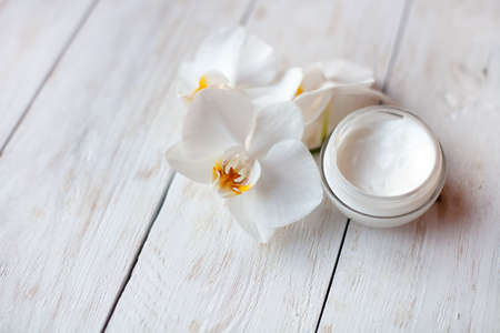 pot of moisturizing face cream and beautiful white orchid flowers Foto de archivo