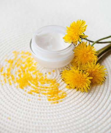 aging skin: Open jar filled with cream and  dandelion on on white background. Fresh light texture of cosmetic product for gentle skincare.
