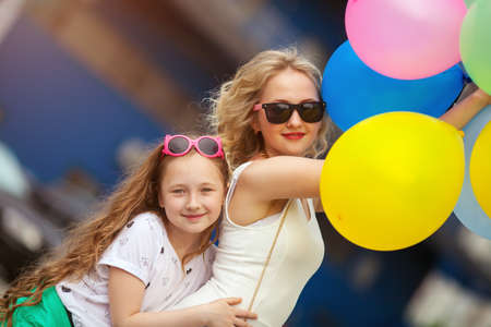 child and sister in trendy sunglasses having fun outdoors with lots of colorful balloons,hugging and laughing.happy family life