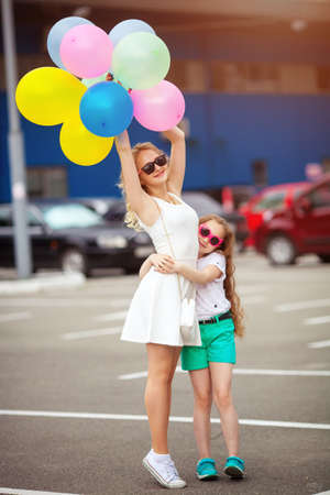 small child and sister in sunglasses having fun outdoors with lots of colorful balloons happy family life. summer holidays happy family life