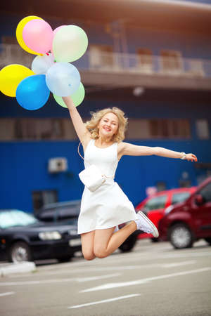 portrait of lovely young blonde jumps from happiness holding balloons concept of a happy life
