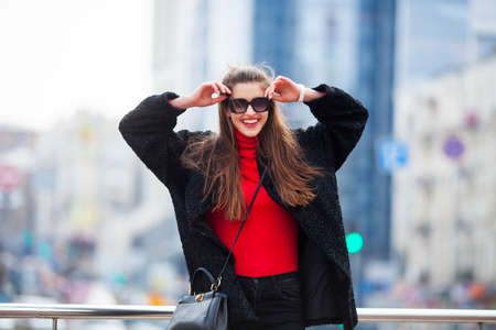 Outdoor lifestyle close up portrait of happy young woman in stylish casual outfit portrait on the street.Pretty hipster girl having fun and enjoying holidays On the background of the big city.