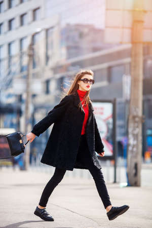 young stylish beautiful woman walking on city street on sunset, europe vacation.Autumn trend,sunglasses, smiling, luxury, red lips, fashionable outfi Stock Photo