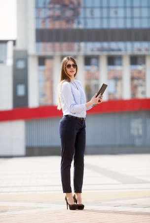 young businesswoman in smart casual stares at the tablet. A successful Manager conducts its business outdoor City business woman working. Stock Photo