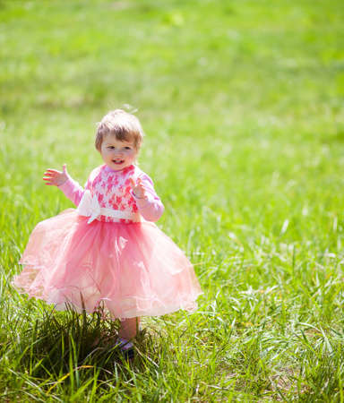 A little girl 1-2 years in fancy dress in the Park. Rejoice and clap their hands. on warm and sunny summer day. copy space