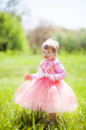 Cute baby girl in fancy dress in the Park. Portrait of cute little cheerful girl outdoors on warm and sunny summer day
