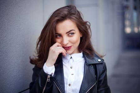 Amazing joyful pretty girl with long brunette hair. posing outdoor. Close up fashion street stile portrait Model looking aside