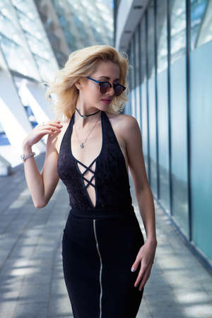 Fashion portrait of young elegant blonde woman outdoor. sunglasses, choker, black skirt and sexy black top Stock Photo