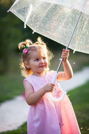 비를 즐기는 어린 소녀 야외 자연에 서 서 귀여운 작은 아이 소녀. 공원에서 우산 아래 예쁜 여자의 초상화를 닫습니다 스톡 콘텐츠