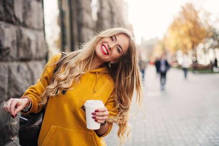 Stilvolle glückliche junge Frau, die boyfrend Jeans trägt, helles gelbes sweetshot der weißen Turnschuhe Sie hält Kaffee zum Mitnehmen. Porträt des lächelnden Mädchens in der Sonnenbrille und in der Tasche