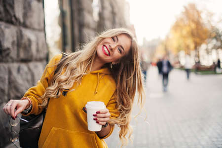 Stylish happy young woman wearing boyfrend jeans, white sneakers bright yellow sweetshot.She holds coffee to go. portrait of smiling girl in sunglasses and bag