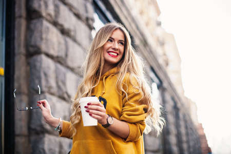 Stylish happy young woman wearing boyfrend jeans, white sneakers bright yellow sweetshot.She holds coffee to go. portrait of smiling girl in sunglasses Street fashion concept Foto de archivo