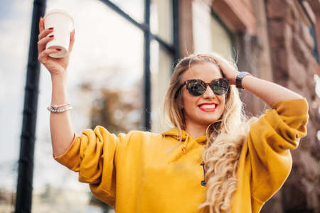 Stylish happy young woman wearing boyfrend jeans, white sneakers bright yellow sweetshot.She holds coffee to go. portrait of smiling girl in sunglasses posing in the street