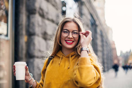 portrait young stylish girl student wearing bright yellow sweatshirt.Close-up portrait of inspired young woman laughing and touching glasses She holds coffee to go