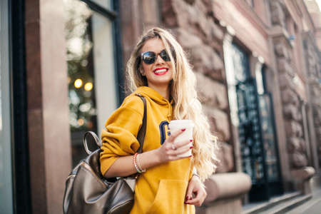 young beautiful blonde drinking coffee walking around the city.mustard sweetshot.,urban backpack , bright red lips Posing against the window of the boutique Model looking aside and smile