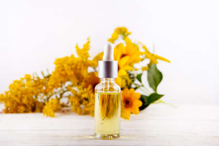 essential oil falling from glass dropper essential oils and medical flowers herbs. Stock Photo