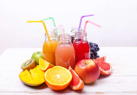 Row Fresh Juices Smoothie five Bottles Red Green pink burgundy Yellow Color Fruits Melon Apple Kiwi Grapes Orange Mango Pomegranate Tropical Selective focus white Wooden Table.