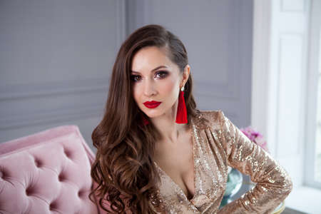 Close up fashion stile portrait of pretty girl in stylish gold shining party dress sits on a pink sofa . Bright smokey eyes make up, red full lips, healthy wavy hairs.