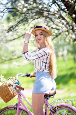 Young woman blonde hair summer style concept.standing near vintage pink bicycle have fun and good mood looking in camera and smiling