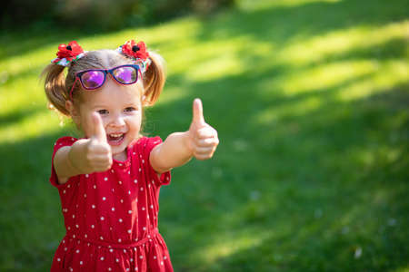 happy funny blonde little girl show sight thumbs up and good luck dressed in a bright red dress and sunglasses. Copy, empty space for text. Stock Photo