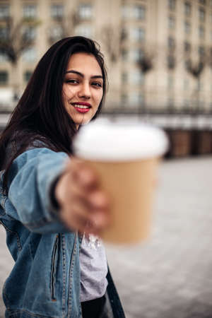 Amazing joyful pretty girl with long brunette hair. posing outdoor. Close up fashion street stile portrait. girl pulls coffee to the camera. Archivio Fotografico