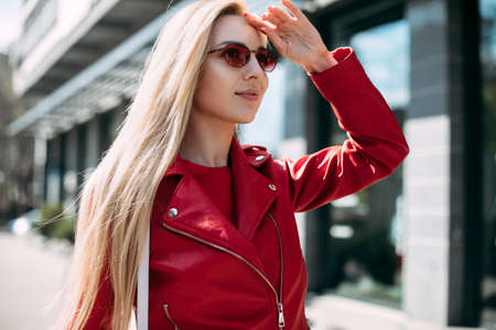 Closeup selfie-portrait student of attractive girl in sunglasses with long hairstyle in city.happy blonde wearing red leather jacket. 版權商用圖片